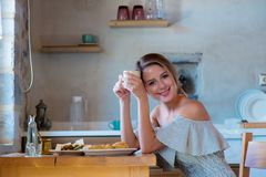 Young girl with cup of coffee or tea on greek kitchen royalty free stock photos