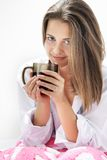 Young girl with cup of tea in bed Royalty Free Stock Photos