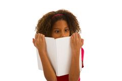 Young girl curisoly looking at book Royalty Free Stock Photos