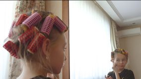 Young girl with curlers on hair removing makeup with cotton sponge front mirror stock footage