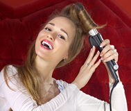 Young girl curling her hair Royalty Free Stock Photo