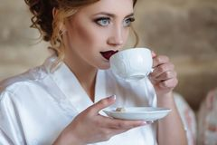 A young girl with curls and red lips drinks coffee in a silk dressing gown. A close-up of the girl is about to take a. Sip from the cup, holding the saucer Stock Photo