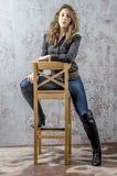 Young girl with curly hair in a black shirt, jeans and high boots cowboy western style. NYoung girl with curly hair in a black shirt, jeans and high boots cowboy stock photos
