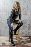 Young girl with curly hair in a black shirt, jeans and high boots cowboy western style. NYoung girl with curly hair in a black shirt, jeans and high boots cowboy royalty free stock images