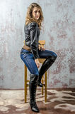 Young girl with curly hair in a black shirt, jeans and high boots cowboy western style. NYoung girl with curly hair in a black shirt, jeans and high boots cowboy stock image