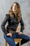 Young girl with curly hair in a black shirt, jeans and high boots cowboy western style Stock Images