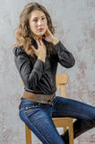 Young girl with curly hair in a black shirt, jeans and high boots cowboy western style Royalty Free Stock Image