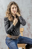 Young girl with curly hair in a black shirt, jeans and high boots cowboy western style Royalty Free Stock Photography