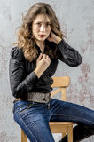 Young girl with curly hair in a black shirt, jeans and high boots cowboy western style. NYoung girl with curly hair in a black shirt, jeans and high boots cowboy stock photo
