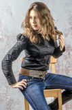 Young girl with curly hair in a black shirt, jeans and high boots cowboy western style Stock Photo