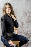 Young girl with curly hair in a black shirt, jeans and high boots cowboy western style. NYoung girl with curly hair in a black shirt, jeans and high boots cowboy stock photography