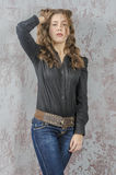Young girl with curly hair in a black shirt, jeans and high boots cowboy western style. NYoung girl with curly hair in a black shirt, jeans and high boots cowboy royalty free stock photo