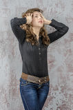 Young girl with curly hair in a black shirt, jeans and high boots cowboy western style. NYoung girl with curly hair in a black shirt, jeans and high boots cowboy royalty free stock image