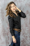 Young girl with curly hair in a black shirt, jeans and high boots cowboy western style. NYoung girl with curly hair in a black shirt, jeans and high boots cowboy royalty free stock photography