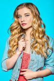 Young girl with curly hair and denim jacket. A young girl with curly hair and denim jacket on a blue background Royalty Free Stock Photography
