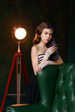 Young girl with curly hair and a fur boa standing with a glass i. N roskoschnogo chair. Gatsby style Stock Images
