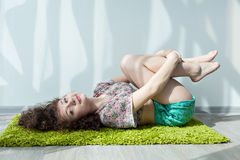 Young girl with curly hair lying on the floor, do stretching exercises. Stock Photo