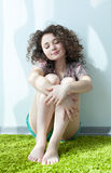 Young girl with curly hair, sitting on the floor hugging his knees Royalty Free Stock Photo