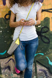 Young girl with curly hair stands near wall with graffiti. She dressed in a white shirt and blue jeans. In her hands mobile phone Stock Photo