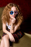 Young girl with curly hair wearing sunglasses with the American Stock Photos