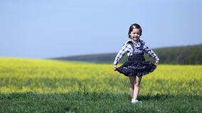 Young girl curtsying or bowing. Cute child bows with a curtsy after dance performance in grass near yellow canola field Royalty Free Stock Photography