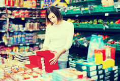 Young girl customer looking for tasty sweets in supermarket Royalty Free Stock Photography