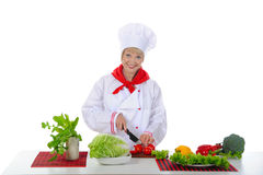Young girl cuts the tomatoes in the kitchen. Royalty Free Stock Photos