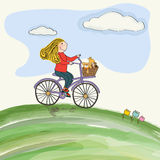 Young girl cycling in the meadow Stock Photos