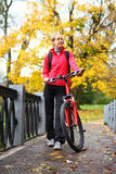 Young girl cyclist with bike on bridge in autumn park Stock Photo