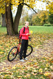 Young girl cyclist with bike enjoy vacation in autumn park Stock Photo