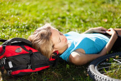 Young girl cyclist enjoying relaxation lying in the fresh grass Royalty Free Stock Photography