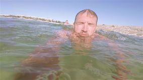 A young girl with dad swim in shallow water in green sea. A young girl with dad swim in shallow water in green sea water. HD stock video