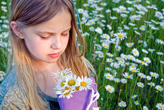 Young girl with daisies in purple sneaker Stock Image