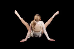 Young girl dance back. A young girl with her back to the camera and her legs in a v shape on a black background Stock Image