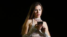 Young girl dancer in ethnic oriental costume uses smartphone outdoor at night.  stock video footage