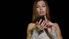 Young girl dancer in ethnic oriental costume uses smartphone outdoor at night.  stock video