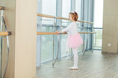 The young girl dances in a ballet tutu in the hall Stock Photo