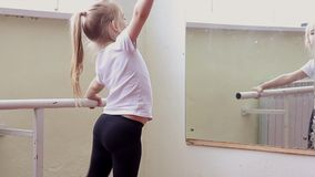 The young girl dances in a ballet tutu in the hall stock video