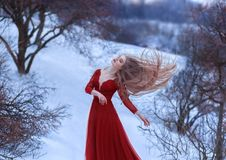 A young girl dances in the wind, her hair is beautifully fluttering. The pose is light and airy, a sense of freedom. Lady in a red dress on a background of a Stock Image