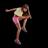 Young girl dancing against black Stock Image