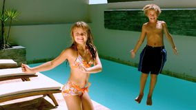 Young girl dancing while brother jumping in the swimming pool stock video
