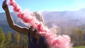 Young girl dancing with the color smoke in the Carpathian mountains in autumn tourist emotional nature stock video footage