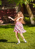 Young girl dancing on grass at sunny day Stock Photo