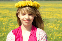Young girl with dandelion wreath. In meadow Stock Image