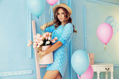 Young girl with dark curly hair and tender makeup, posing with colorful air balloons. Fashion interior photo of beautiful young girl with dark curly hair and stock image