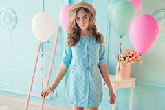 Young girl with dark curly hair and tender makeup, posing with colorful air balloons. Fashion interior photo of beautiful young girl with dark curly hair and royalty free stock images