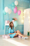 Young girl with dark curly hair and tender makeup, posing with colorful air balloons. Fashion interior photo of beautiful young girl with dark curly hair and royalty free stock photos