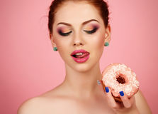 Young girl with dark hair and bright makeup holding sweet donuts Stock Image