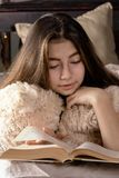 A young girl with dark hair is lying in bed and reading a book. Woman hugging a toy bear. Calm evening photo royalty free stock image