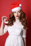 Young girl with dark hair wears elegant dress and Santa hat Stock Photo